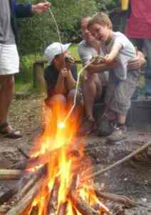 Child and man next to campfire
