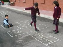 3 children playing hopscotch