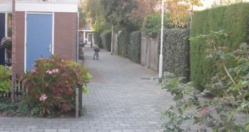 Dutch child riding away on a bike