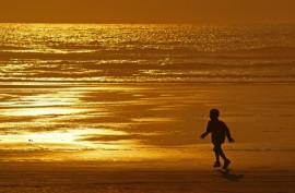 child on a beach at sunset