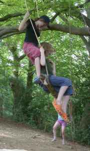 Two children on a tree swing trapeze
