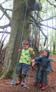 3 young children swinging on a rope swing in the woods