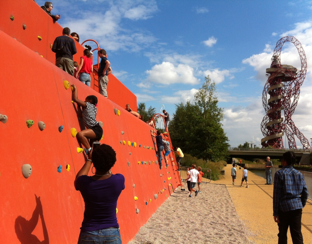 Woman photographing child on Olympic Park climbing wall