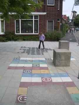 Child playing on pavement in residential area of Delft