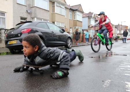 Boy lying on skateboard in street with child cyclist behind