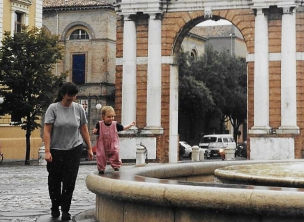 Toddler walking on a fountain wall next to her mother